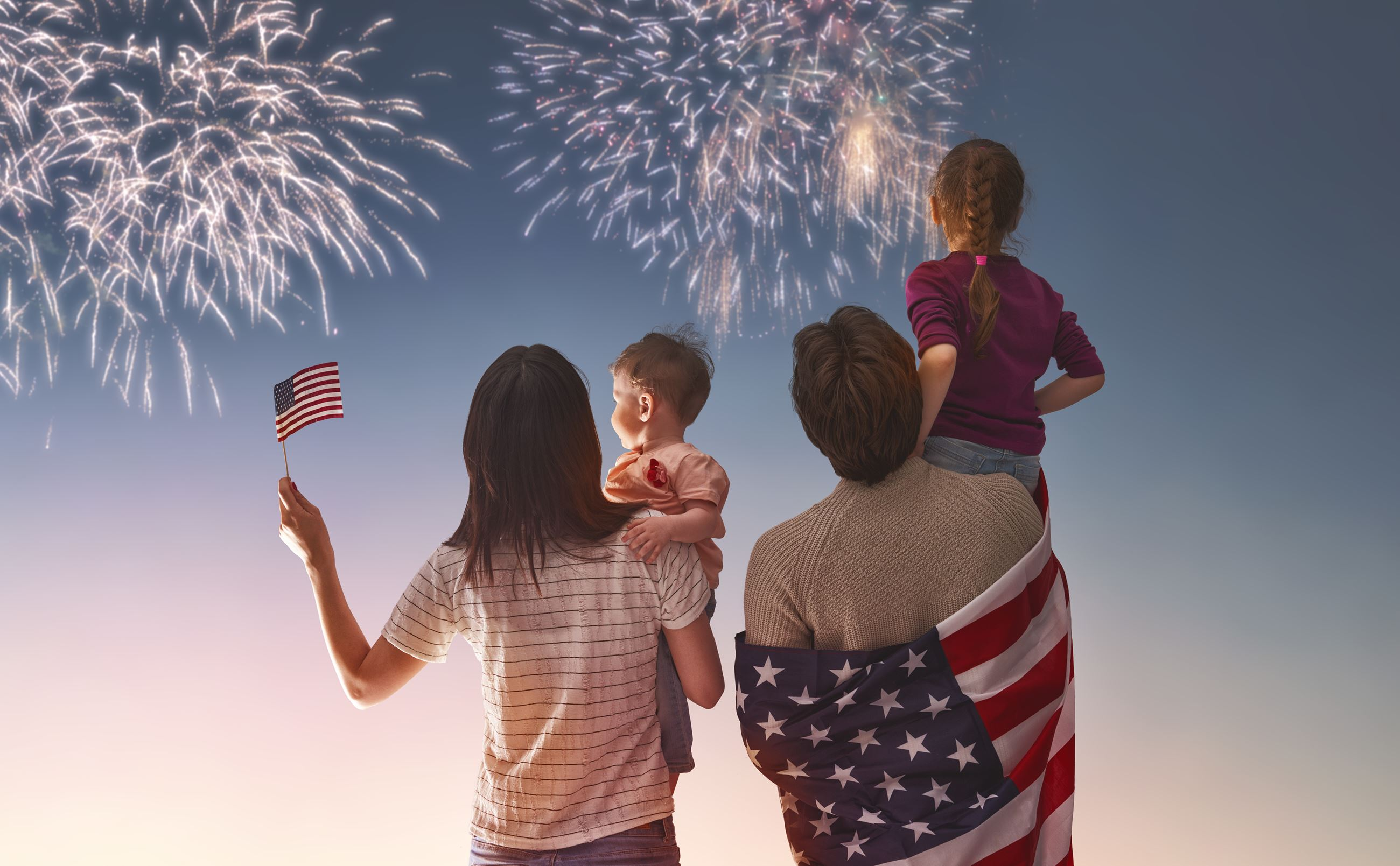 Two adults holding two kids watching fireworks show
